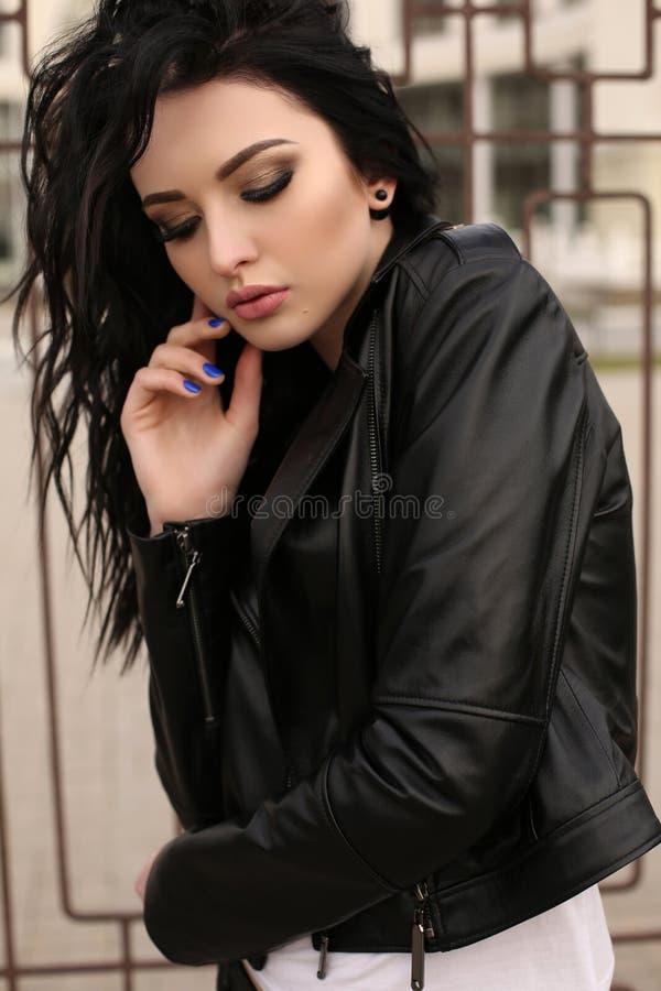 Jeune femme magnifique avec les cheveux foncés dans des vêtements sport posant  photographie stock libre de droits