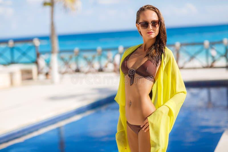 foto de Jeune Femme Magnifique Posant Dans Le Bikini Avec Le Pareo Jaune Près De La Piscine Image stock
