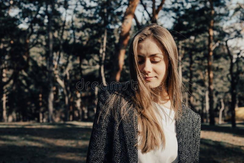 Jeune femme magnifique posant sur l'appareil-photo sur le fond d'arbres en parc photos stock