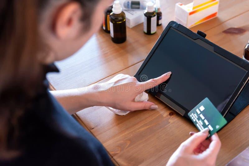 Jeune femme malade à la maison payant des mdeicines sur le comprimé numérique à côté des médecines image stock