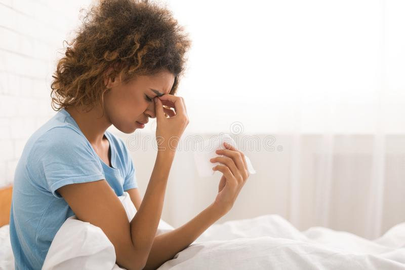 Jeune femme malade avec la grippe soufflant son nez images stock