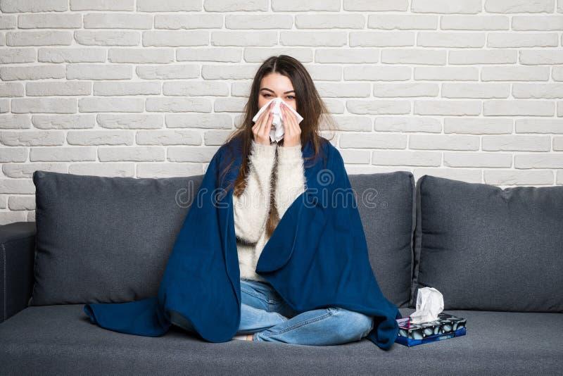 Jeune femme malade s'asseyant sur le sofa soufflant son nez à la maison photo stock