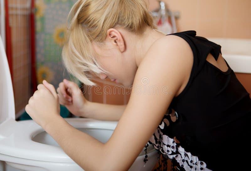 Jeune femme malade se penchant sur le siège des toilettes ouvert image libre de droits