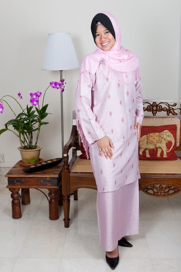 Jeune femme malaise dans le kurung rose de baju, photo libre de droits