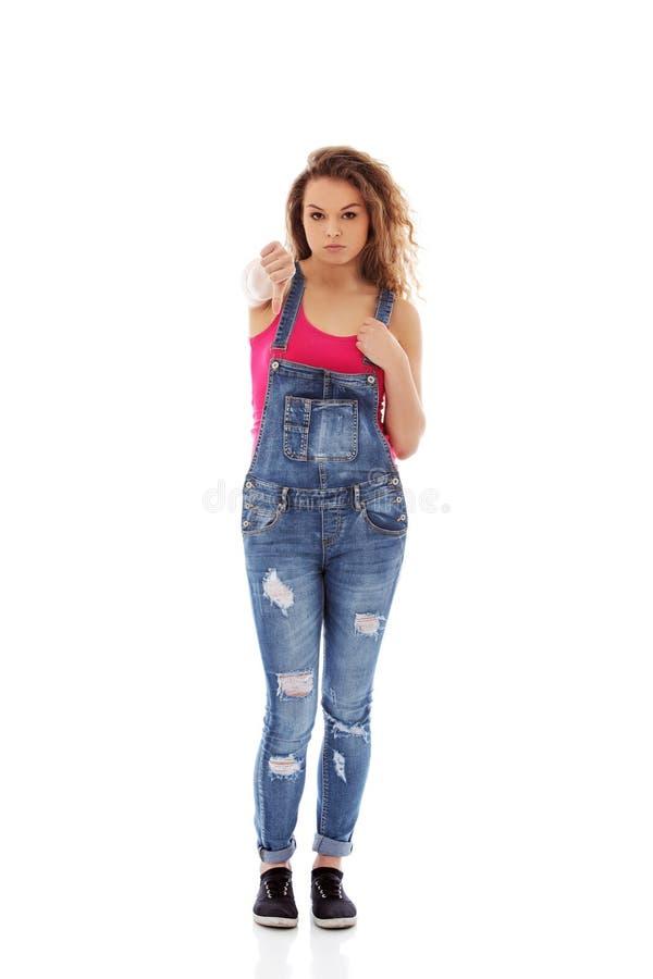 Jeune femme malheureuse avec des pouces vers le bas images stock