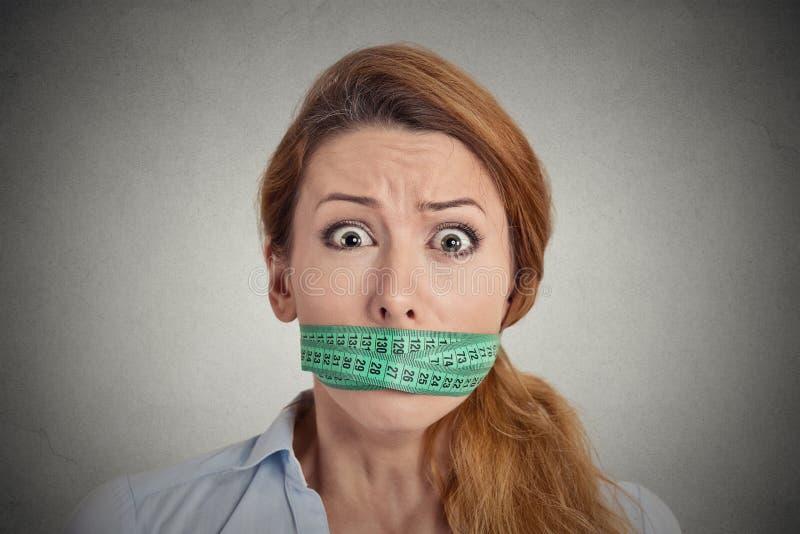 Jeune femme malheureuse avec la bouche de mesure de bâche de bande images libres de droits