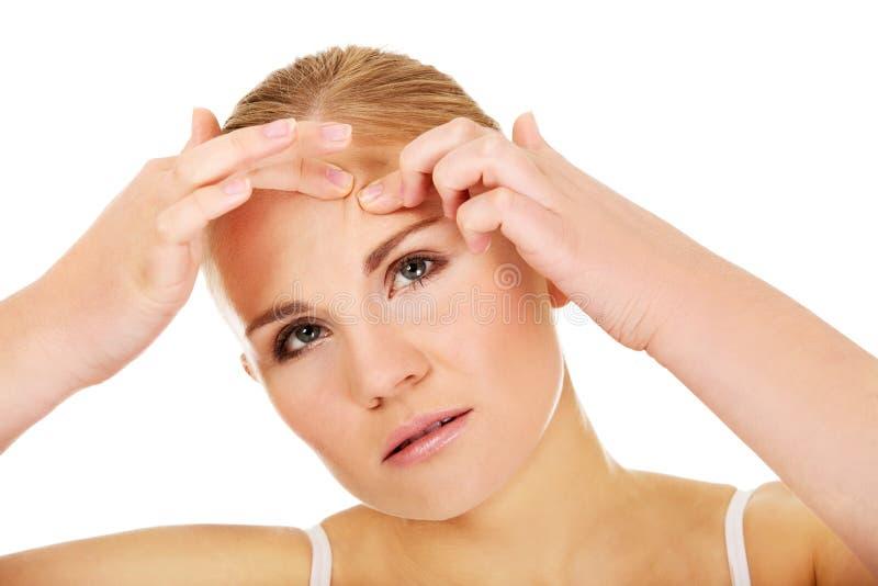 Jeune femme malheureuse serrant le bouton sur le visage image stock