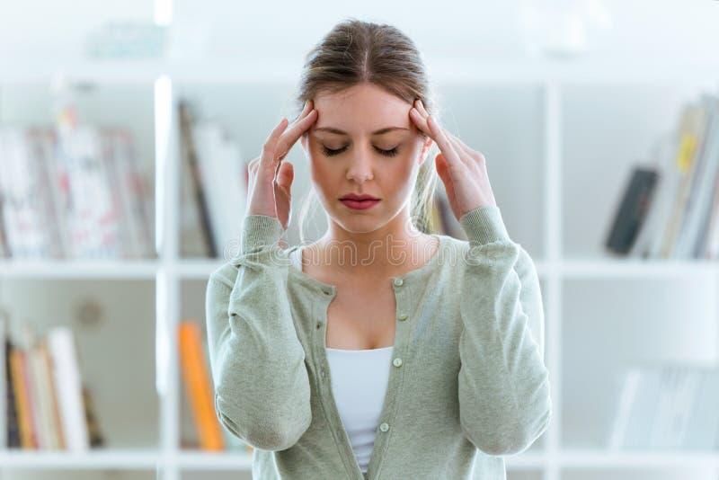 Jeune femme malsaine avec le mal de tête touchant sa tête à la maison image libre de droits