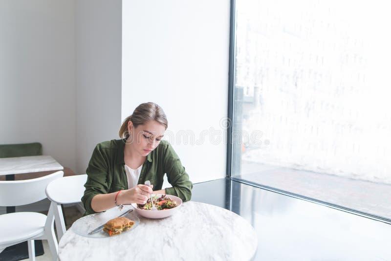Jeune femme mangeant d'une salade à une table à la fenêtre dans un restaurant avec un intérieur léger image stock