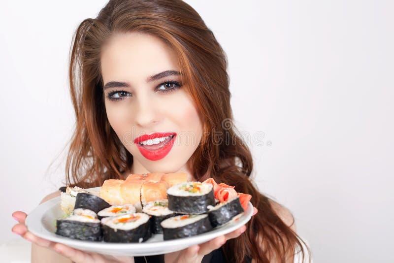 Jeune femme mangeant des sushi au restaurant japonais images libres de droits