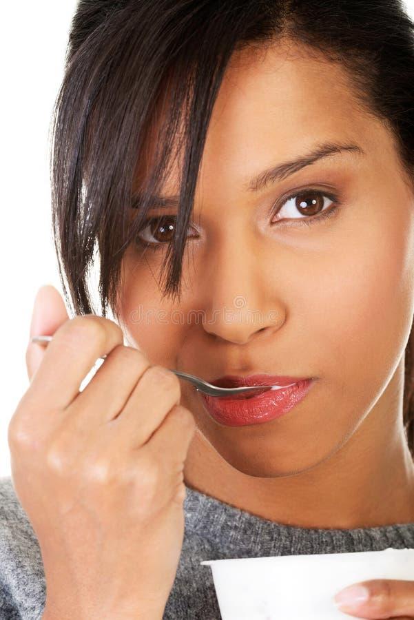 Jeune femme mangeant du yaourt en tant que le petit déjeuner ou casse-croûte sain. image stock