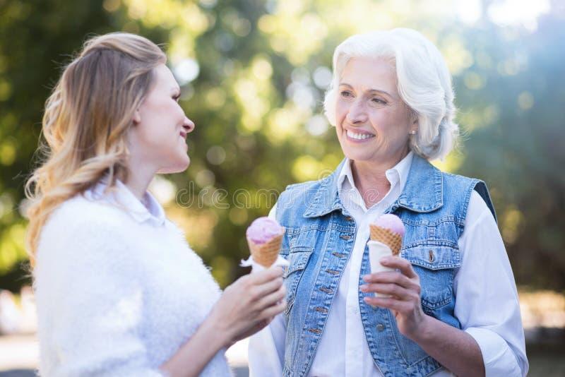 Jeune femme mangeant la crème glacée avec la mère âgée dehors images stock