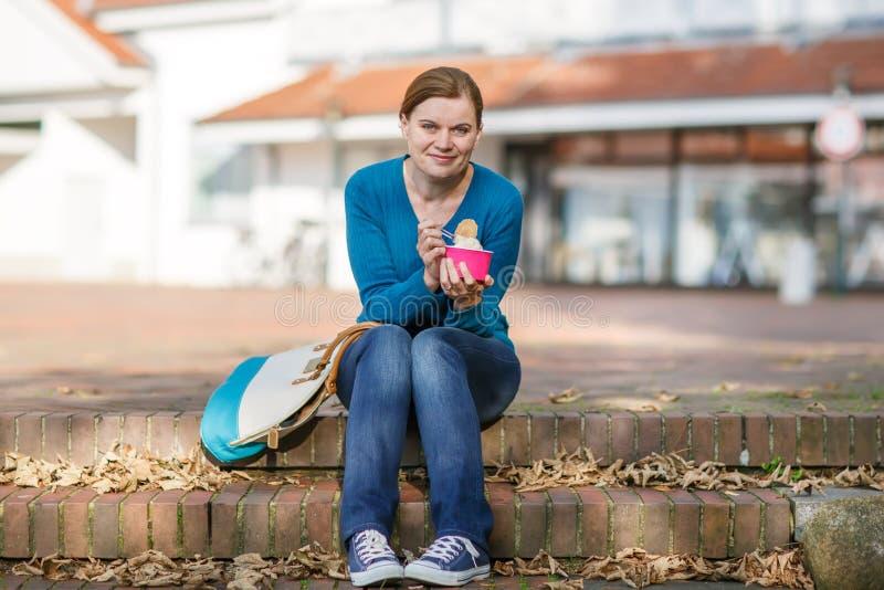 Jeune femme mangeant la crème glacée en parc d'été. photographie stock