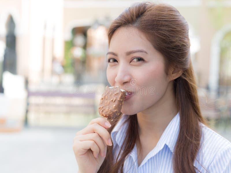 Jeune femme mangeant la crême glacée images stock