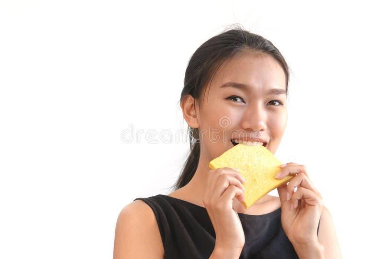 jeune femme mangeant la tranche de pain image stock
