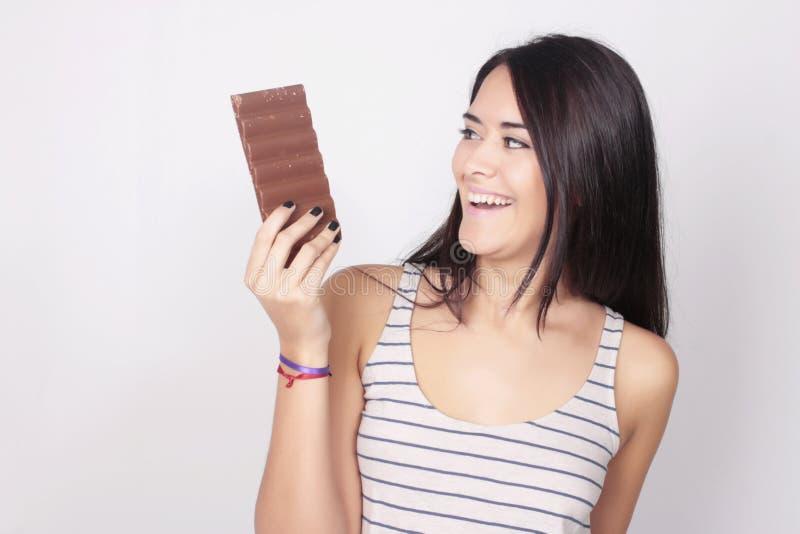 Jeune femme mangeant une barre de chocolat images stock