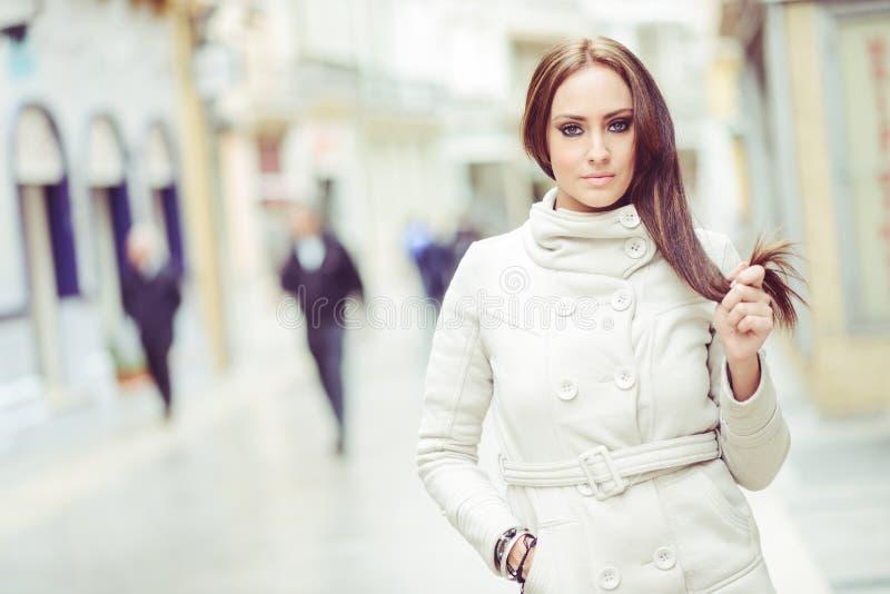 Jeune femme, manteau blanc de port, avec de longs cheveux image libre de droits