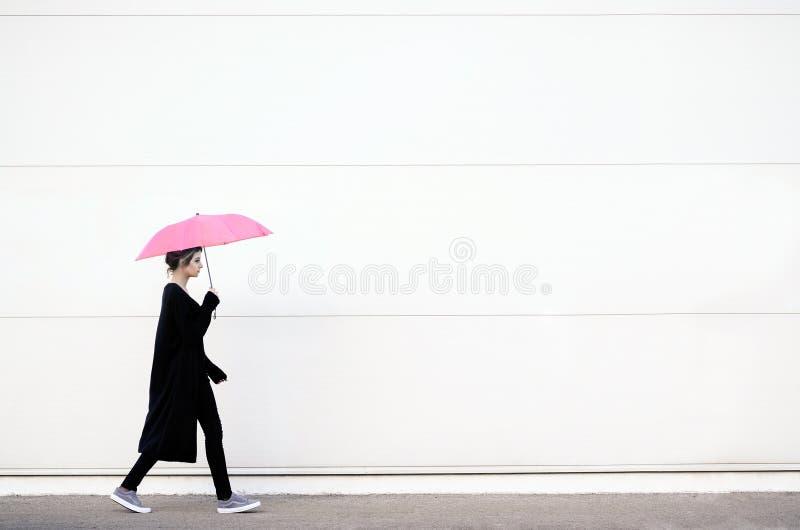 Jeune femme marchant avec le parapluie rose image stock