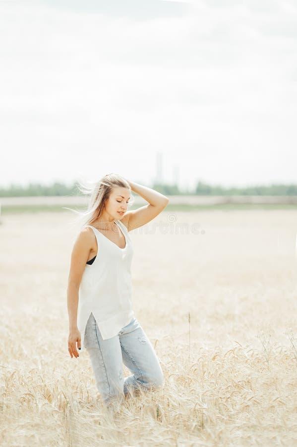 Jeune femme marchant dans le domaine de blé Sc?ne rurale images libres de droits