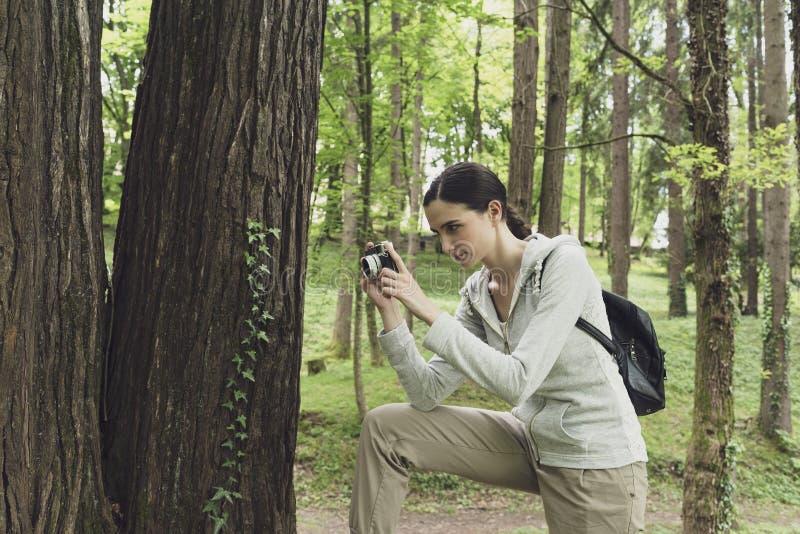 Jeune femme marchant en nature et prenant des photos image stock