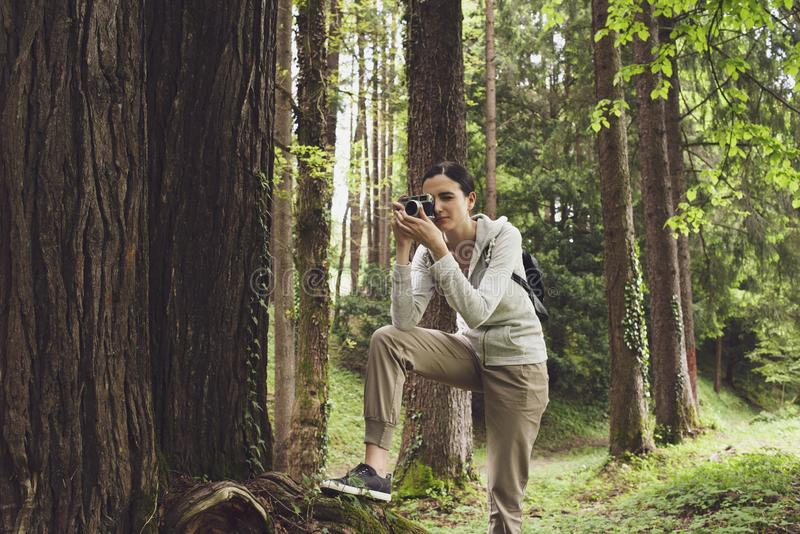 Jeune femme marchant en nature et prenant des photos photographie stock