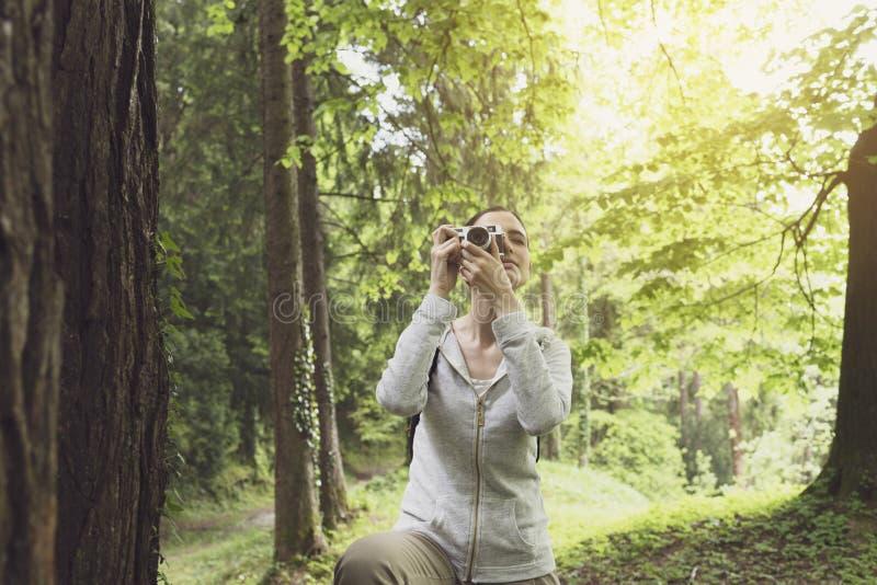 Jeune femme marchant en nature et prenant des photos photos libres de droits