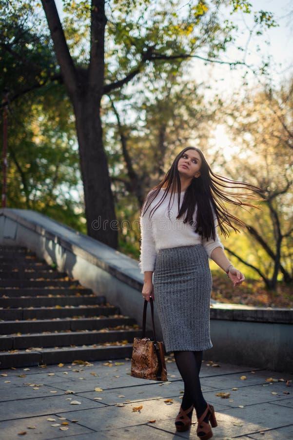 jeune femme marchant en parc ensoleillé de ville photographie stock libre de droits
