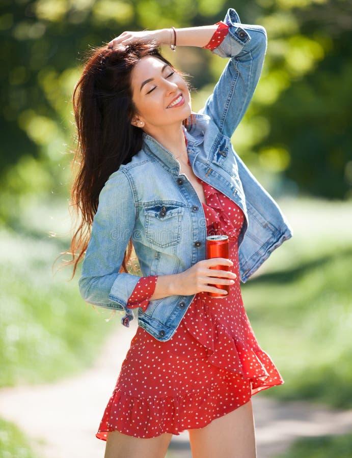 Jeune femme marchant en stationnement Sc?ne de nature de beaut? avec le fond color? Femme de mode avec la bouteille de la boisson photographie stock