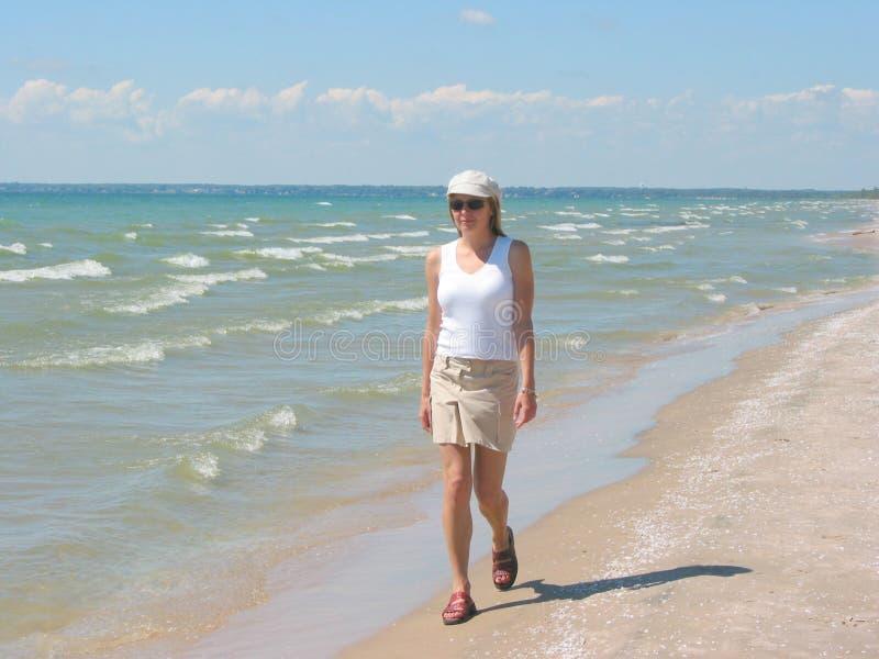 Jeune femme marchant sur la plage photo stock