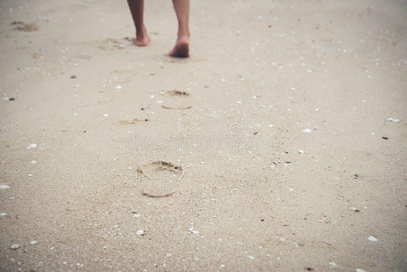 Jeune femme marchant sur la plage avec nu-pieds photographie stock libre de droits
