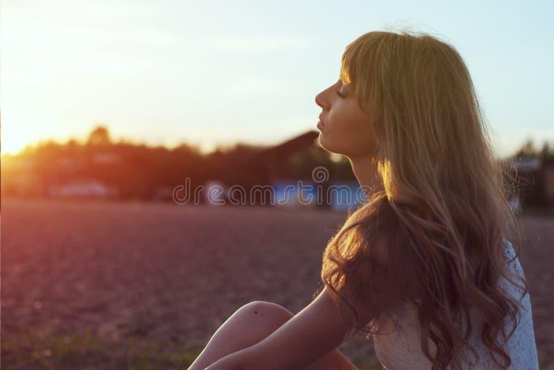 Jeune femme marchant sur la plage sous la lumière de coucher du soleil, photos stock