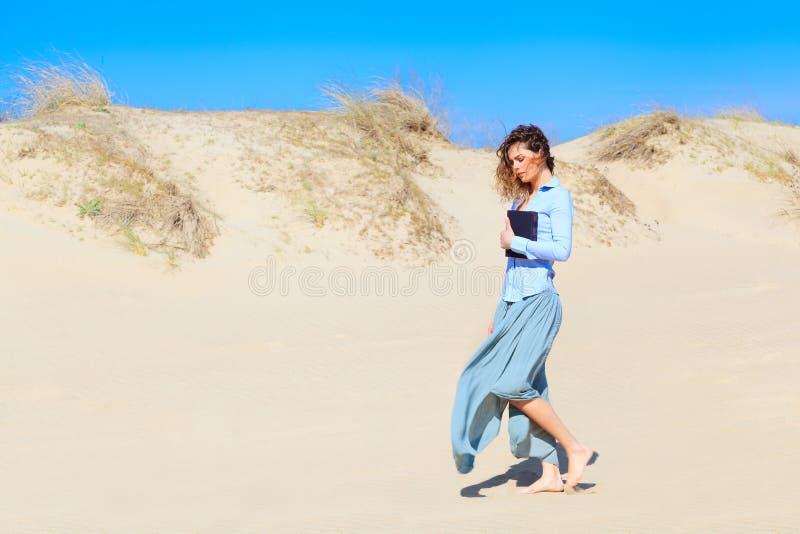 Jeune femme marchant sur le bord de la mer photo stock