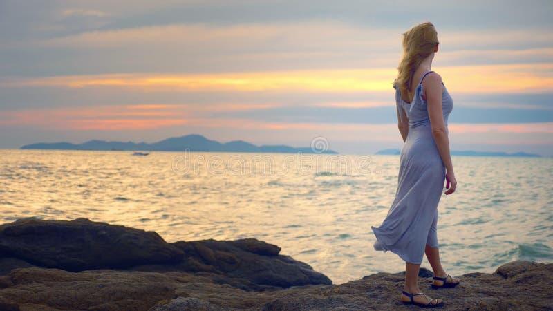 Jeune femme marchant sur un rocheux et appréciant la vue du coucher du soleil, éclaboussant des vagues images stock