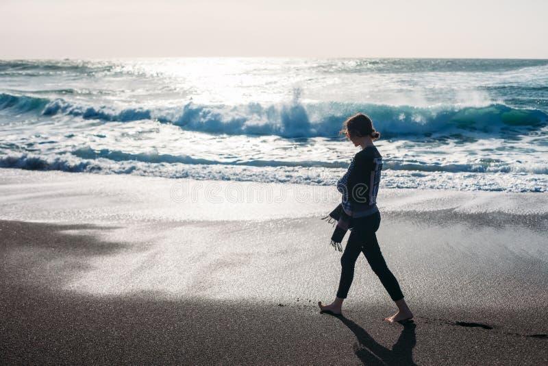 Jeune femme marchant sur une plage noire vide de sable photographie stock libre de droits