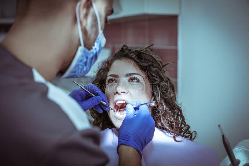 Jeune femme masculine de chirurgie de dentiste photo libre de droits