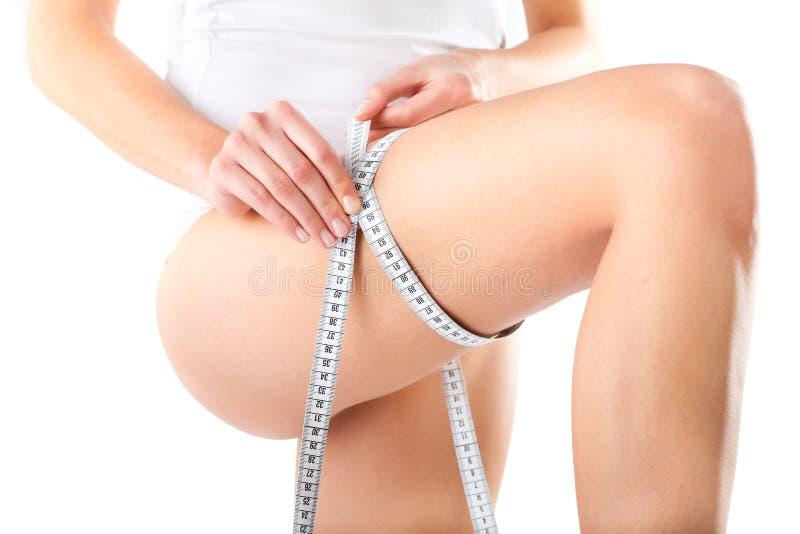 Jeune femme mesurant sa cuisse photo stock