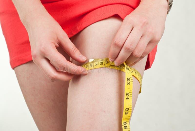 Jeune femme mesurant sa cuisse image libre de droits