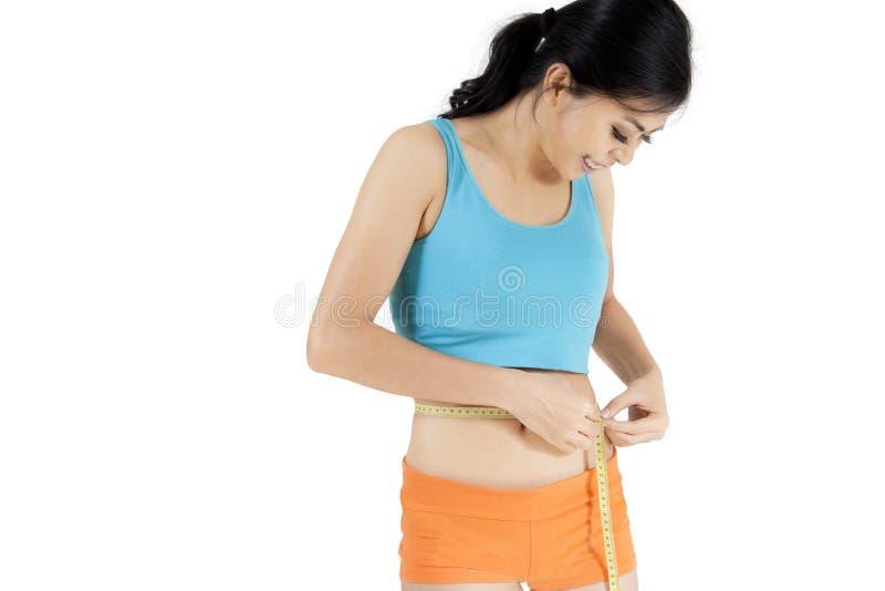 Jeune femme mesurant sa taille mince photographie stock