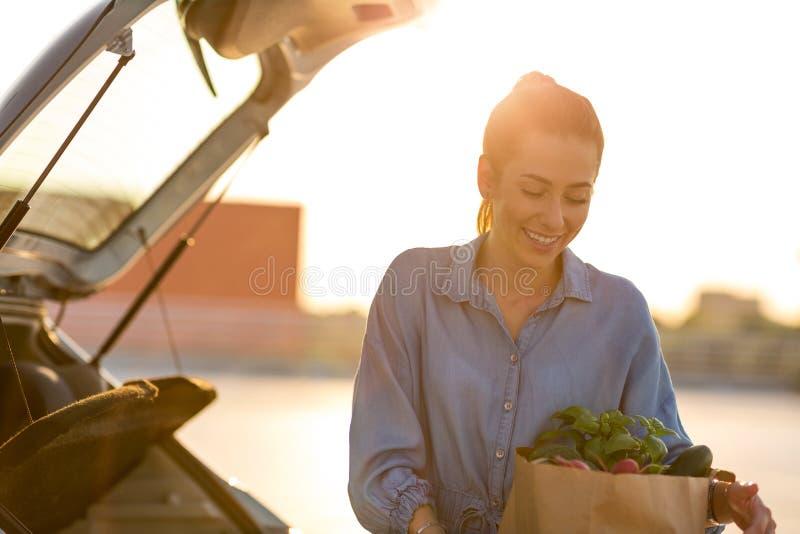 Jeune femme mettant des épiceries au tronc de voiture photo stock