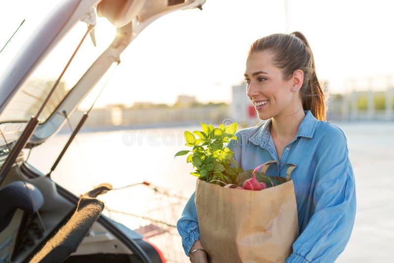 Jeune femme mettant des épiceries au tronc de voiture photos libres de droits