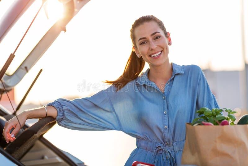 Jeune femme mettant des épiceries au tronc de voiture photo libre de droits