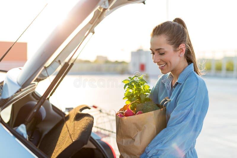 Jeune femme mettant des épiceries au tronc de voiture photos stock