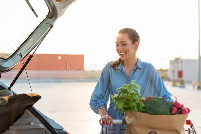 Jeune femme mettant des épiceries au tronc de voiture photographie stock libre de droits