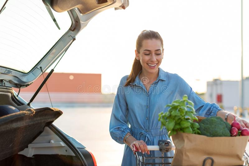 Jeune femme mettant des épiceries au tronc de voiture images libres de droits