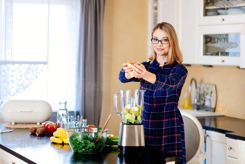 Jeune femme mettant des fruits et légumes dans le mélangeur eletrical photographie stock