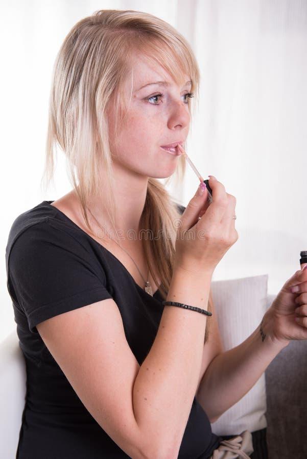 Jeune femme mettant des lipgloss avec une brosse sur ses lèvres photos libres de droits
