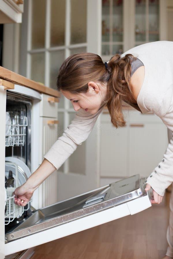 Jeune femme mettant des paraboloïdes dans le lave-vaisselle photos libres de droits