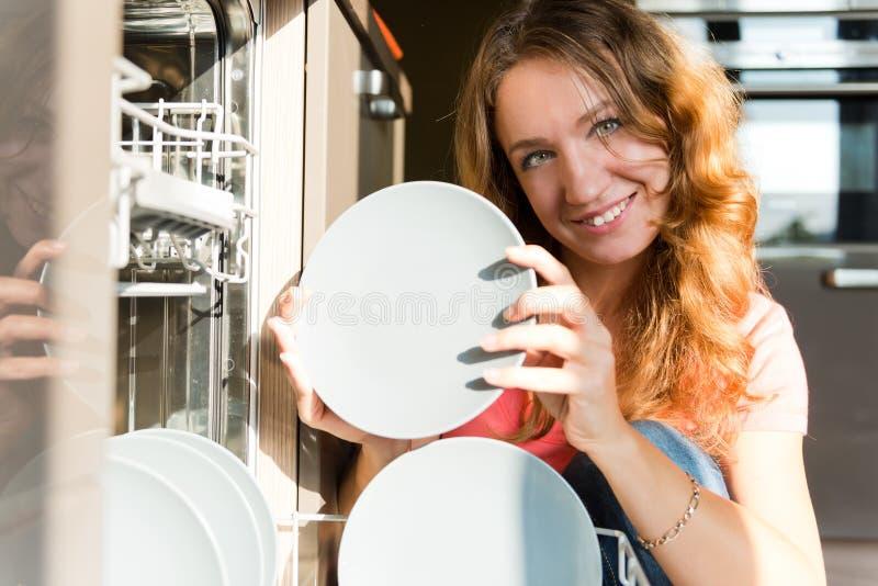 Jeune femme mettant des plats dans le lave-vaisselle photographie stock libre de droits