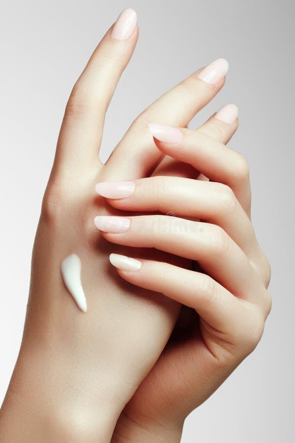 Jeune femme mettant la crème sur sa main photographie stock