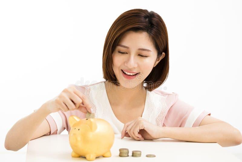 Jeune femme mettant la pièce de monnaie à la tirelire photo libre de droits
